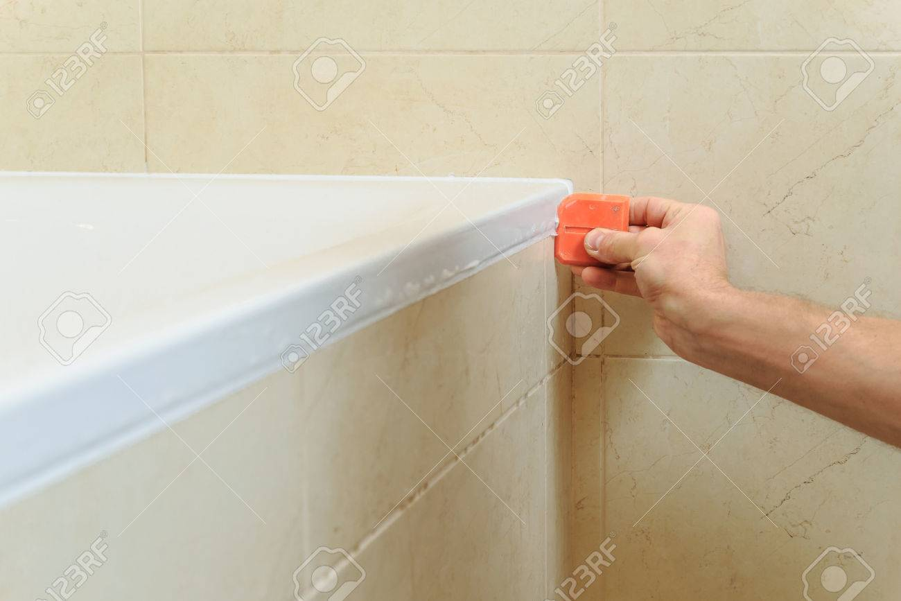 Worker Puts Silicone Sealant To Caulk The Joint Between Tub And ...
