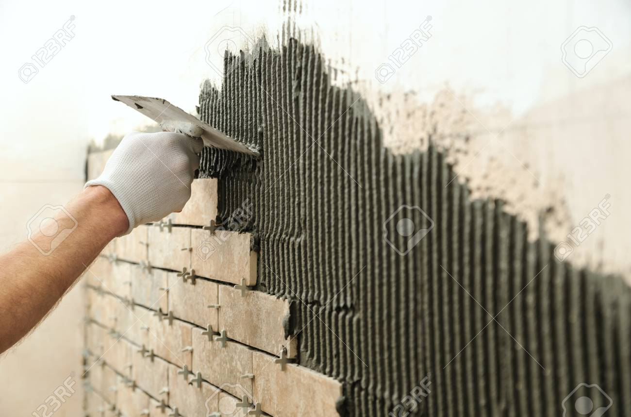 Installing The Tiles On The Wall. A Worker Setting Tiles In The ...