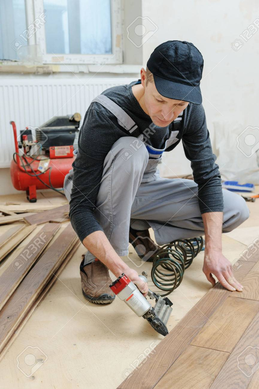Installing A Wooden Floor The Worker Fixes The Board Using A