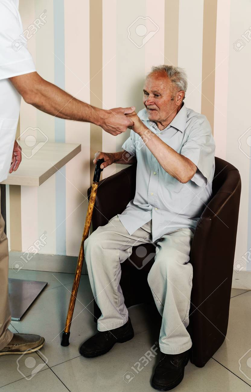 The Doctor Is Helping The Old Man Get Up From The Chair. Stock Photo ...