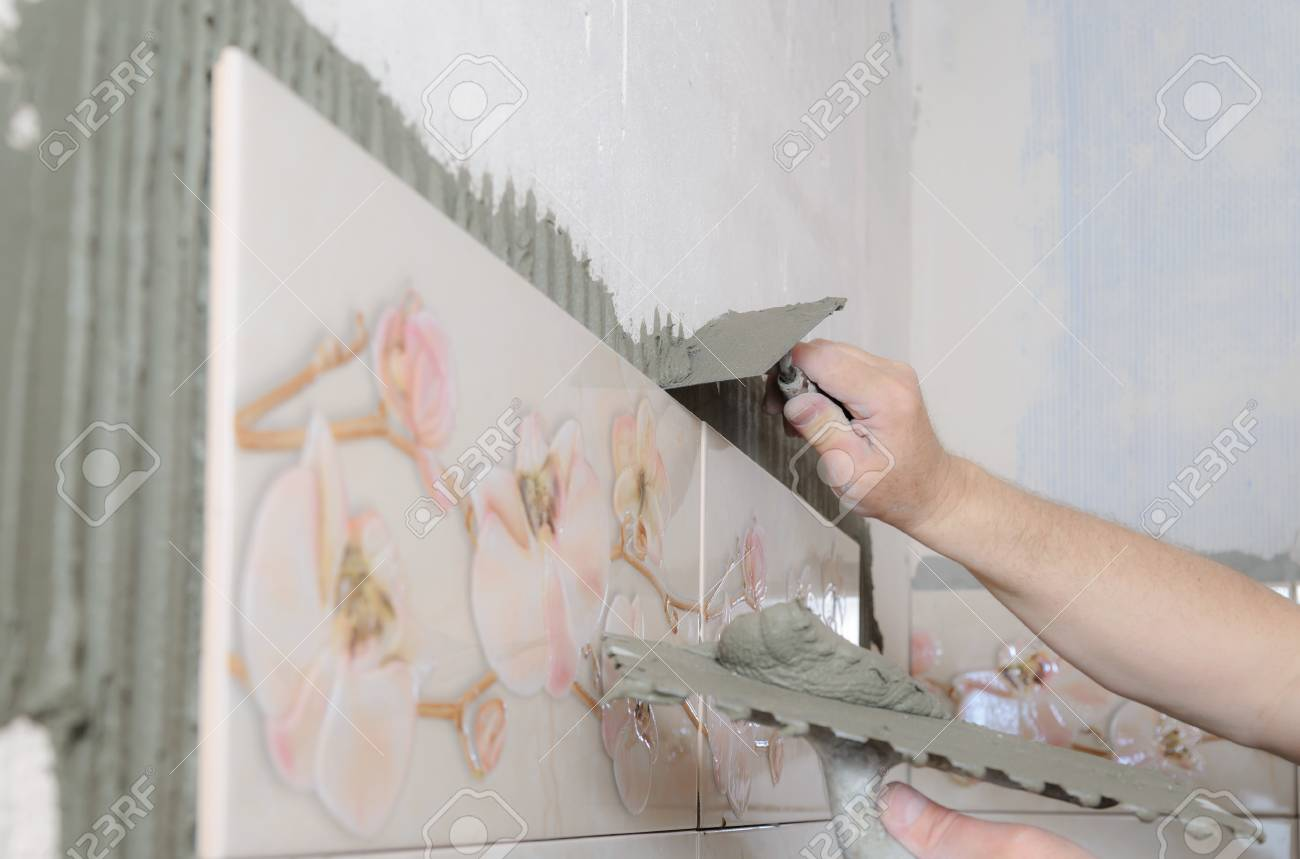 Tilers Hands Are Putting On A Tile Adhesive On The Wall In The ...