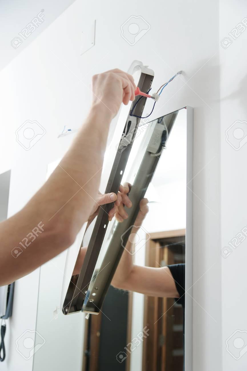 Installieren Der Lampe über Dem Spiegel. Der Mann Verbindet Die ...