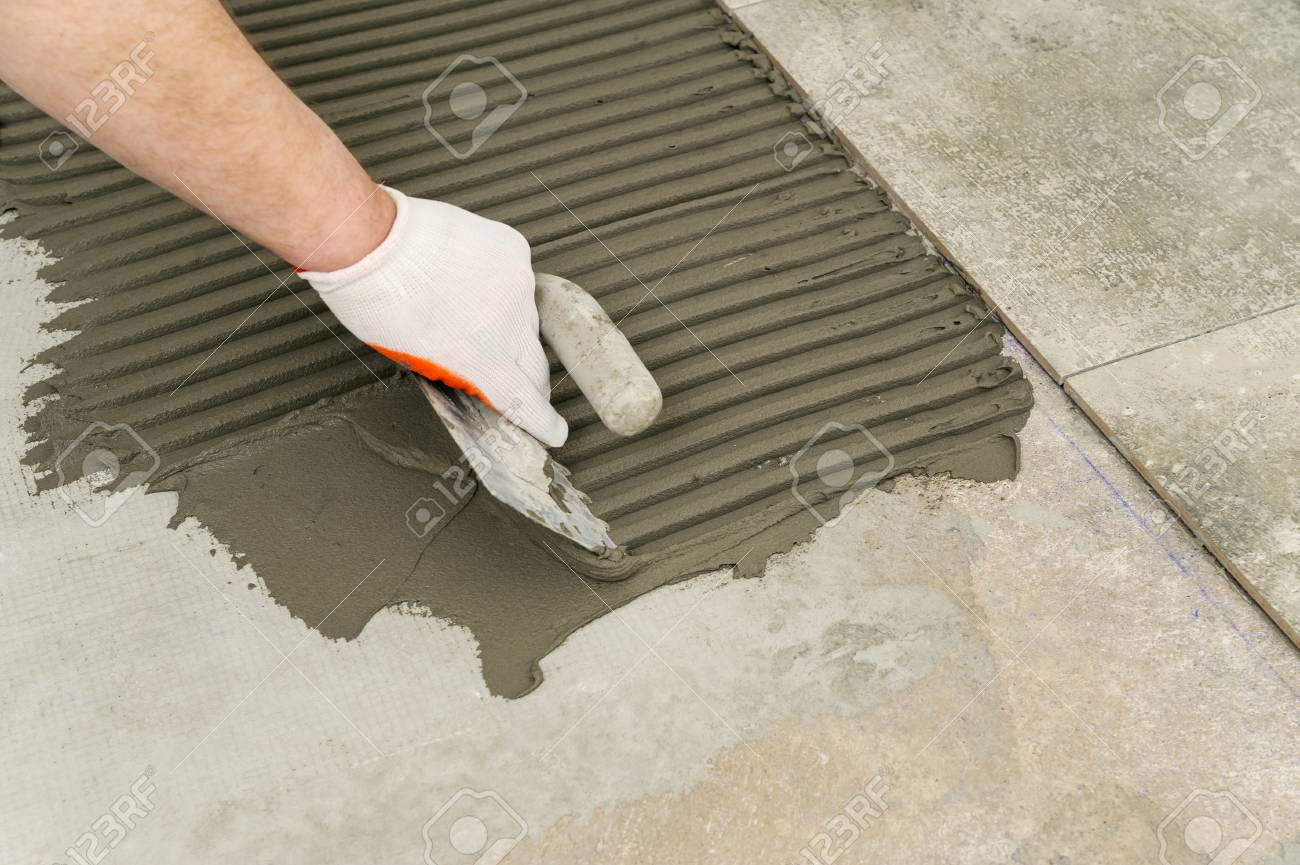 Laying Ceramic Tiles Troweling Mortar Onto A Concrete Floor Stock
