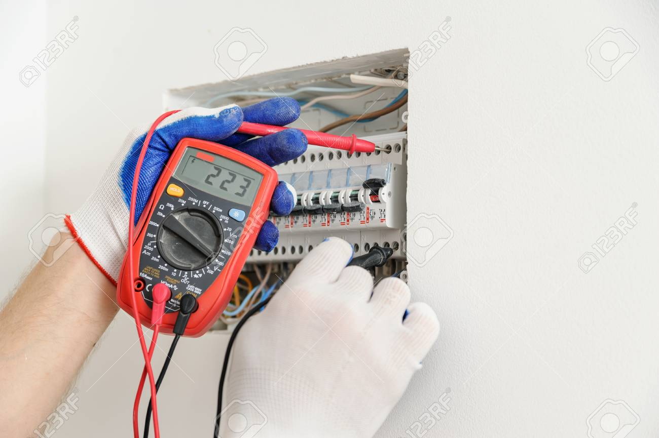 electrician check voltage in electrical fuse box with a multimeter  stock  photo - 101171741
