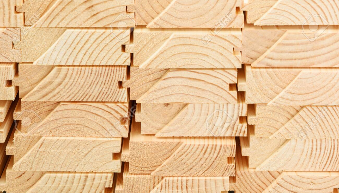End view of stacked floorboards. Wooden structure closeup. - 129909964