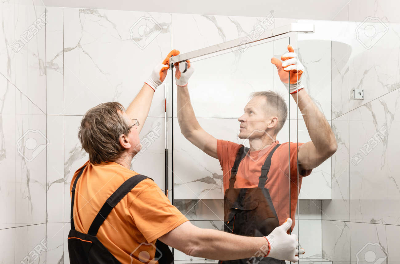 Workers are installing glass door of the shower enclosure. - 167444852
