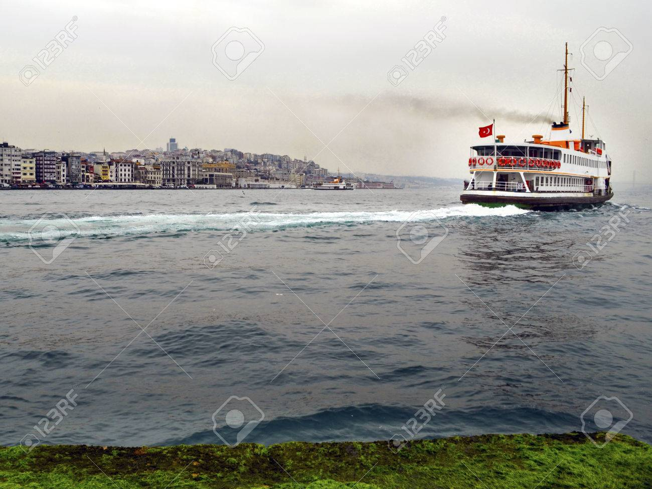 Ferry in Istanbul Bosphorus. Most Istanbulites commute from Europe to Asia on one of the dozen ferries that crisscross the Bosphorus all day long. - 70431388