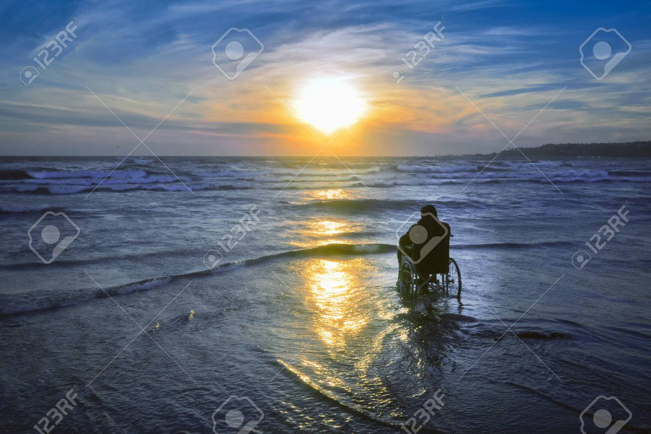 Sunset on the beach handicapped man in wheelchair. - 70810050