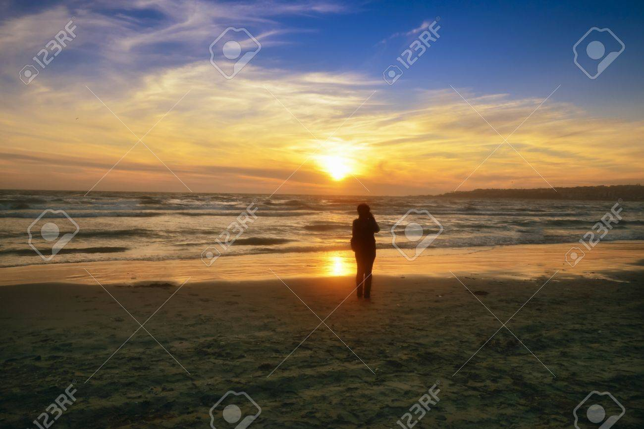 Sunset over the sea, beach, sea and sun orange colors. Silhouettes of people appearing. - 71015255