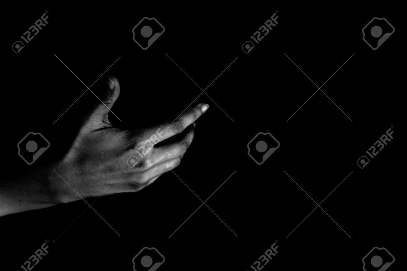 Hand of woman reaching out from the dark - 104769230