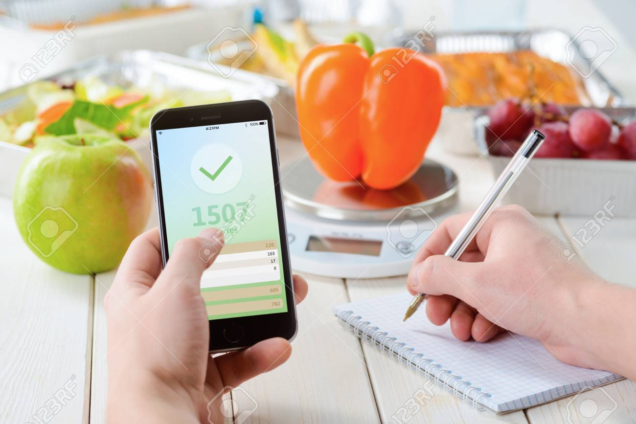 Calorie counter app on the smartphone, making notes, close-up. Grapes, an apple on the wooden surface, a pepper on the food scale on the background. Weight loss journey. - 107007223