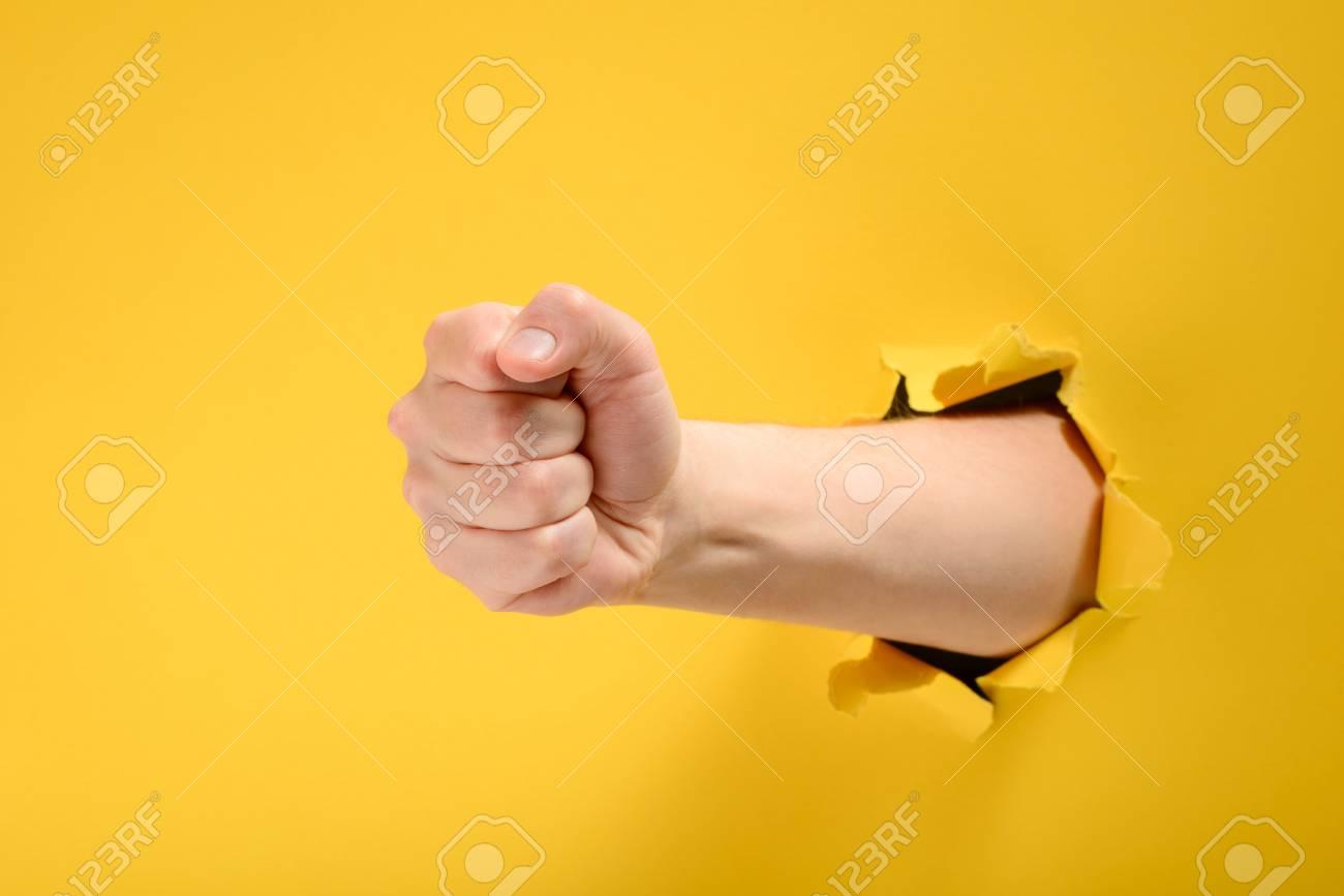 Fist punching through yellow paper - 118736182