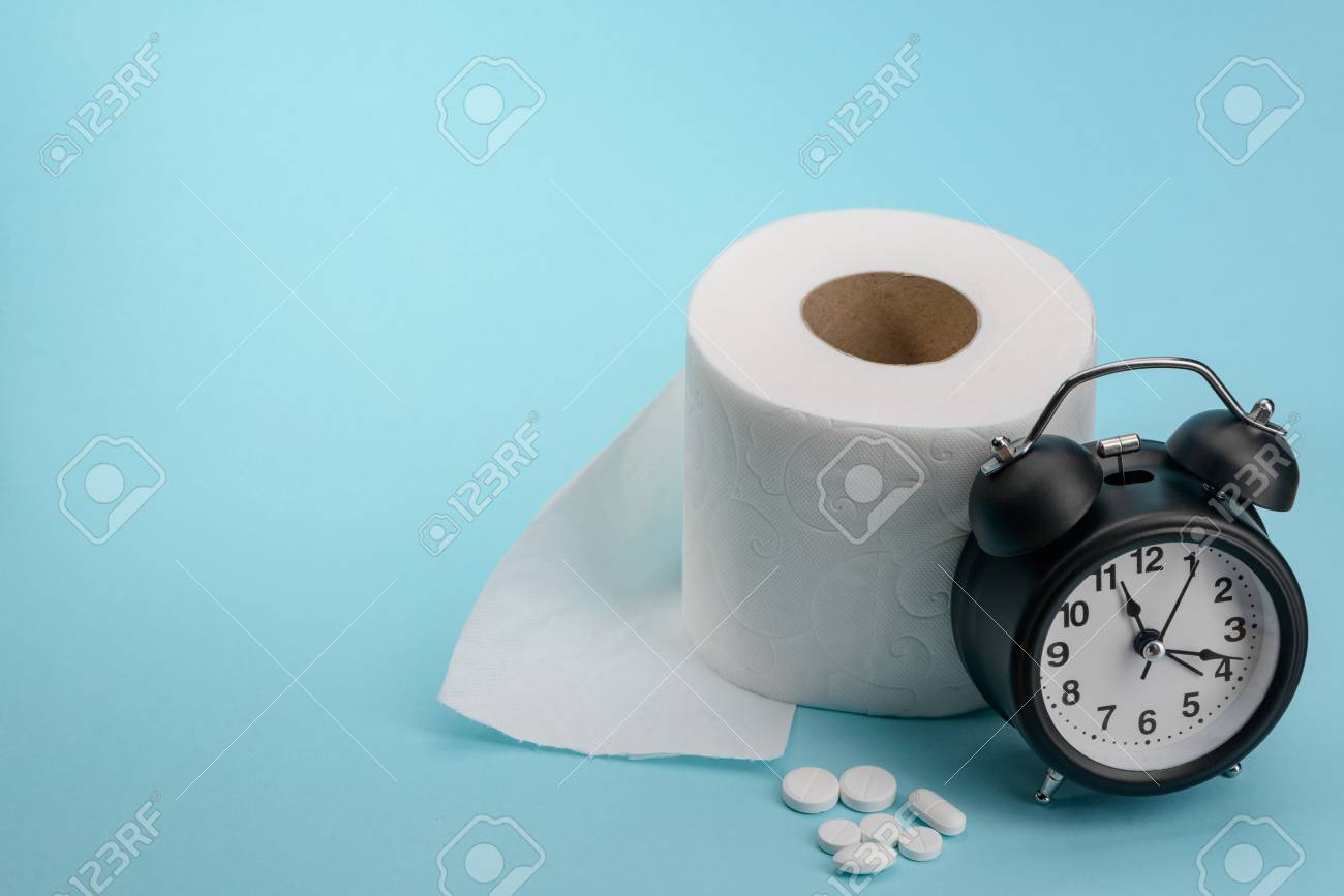 Toilet paper, pills and alarm clock on blue background. Diarhhea or constipation cure. Medical commercial concept. - 120815657
