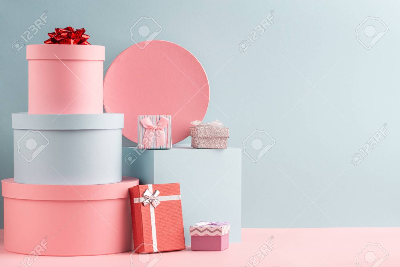 Pink and turquoise round gift boxes and red fir tree on teal background - 134781930