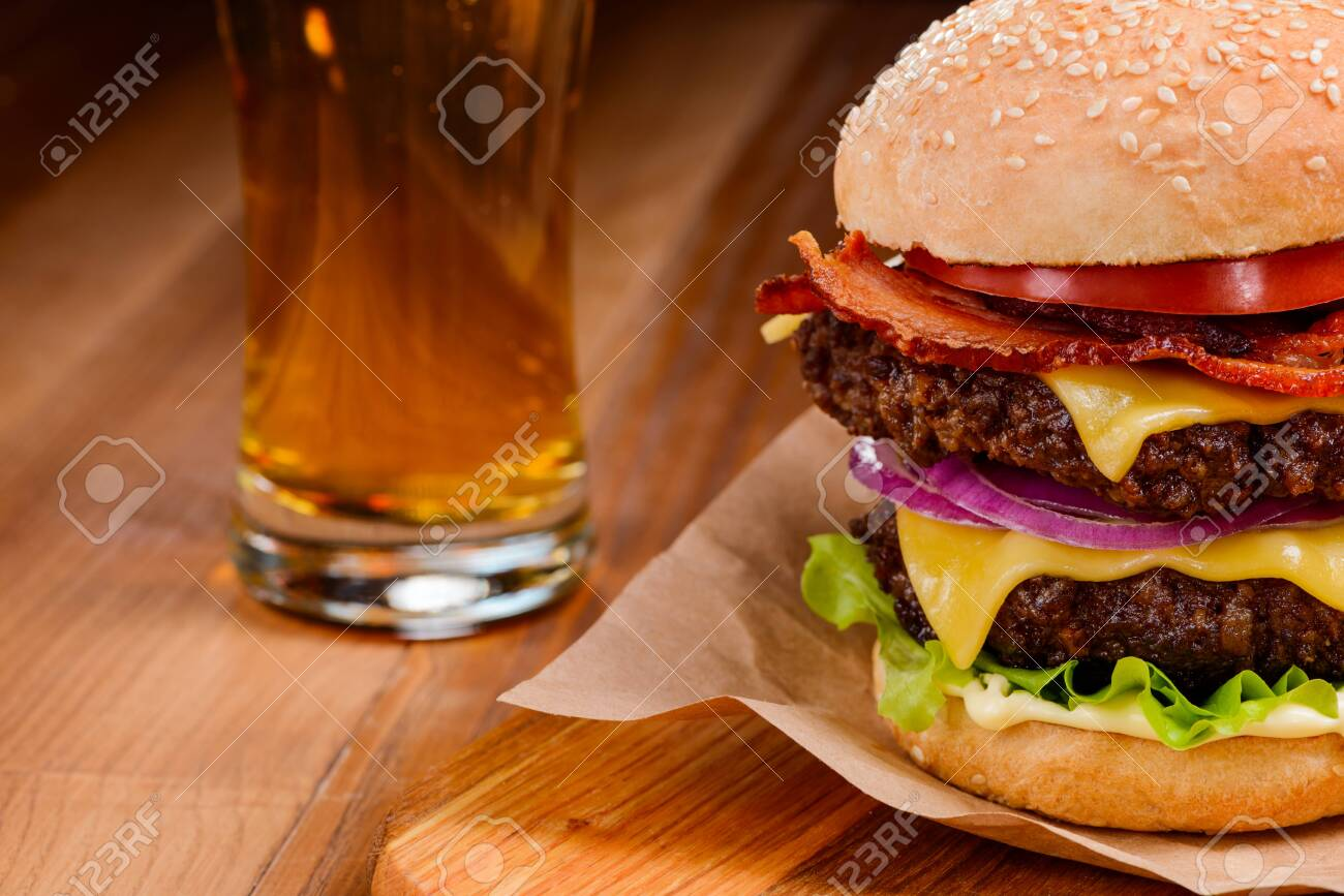 Double hamburger and beer on a wooden table, selective focus - 151566037