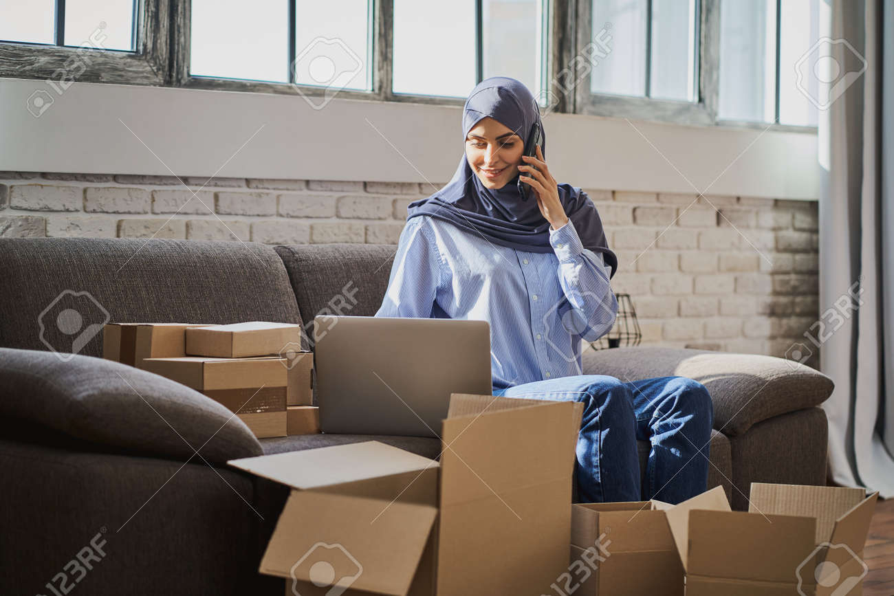 Muslim woman talking on the phone and looking at a laptop - 171608627