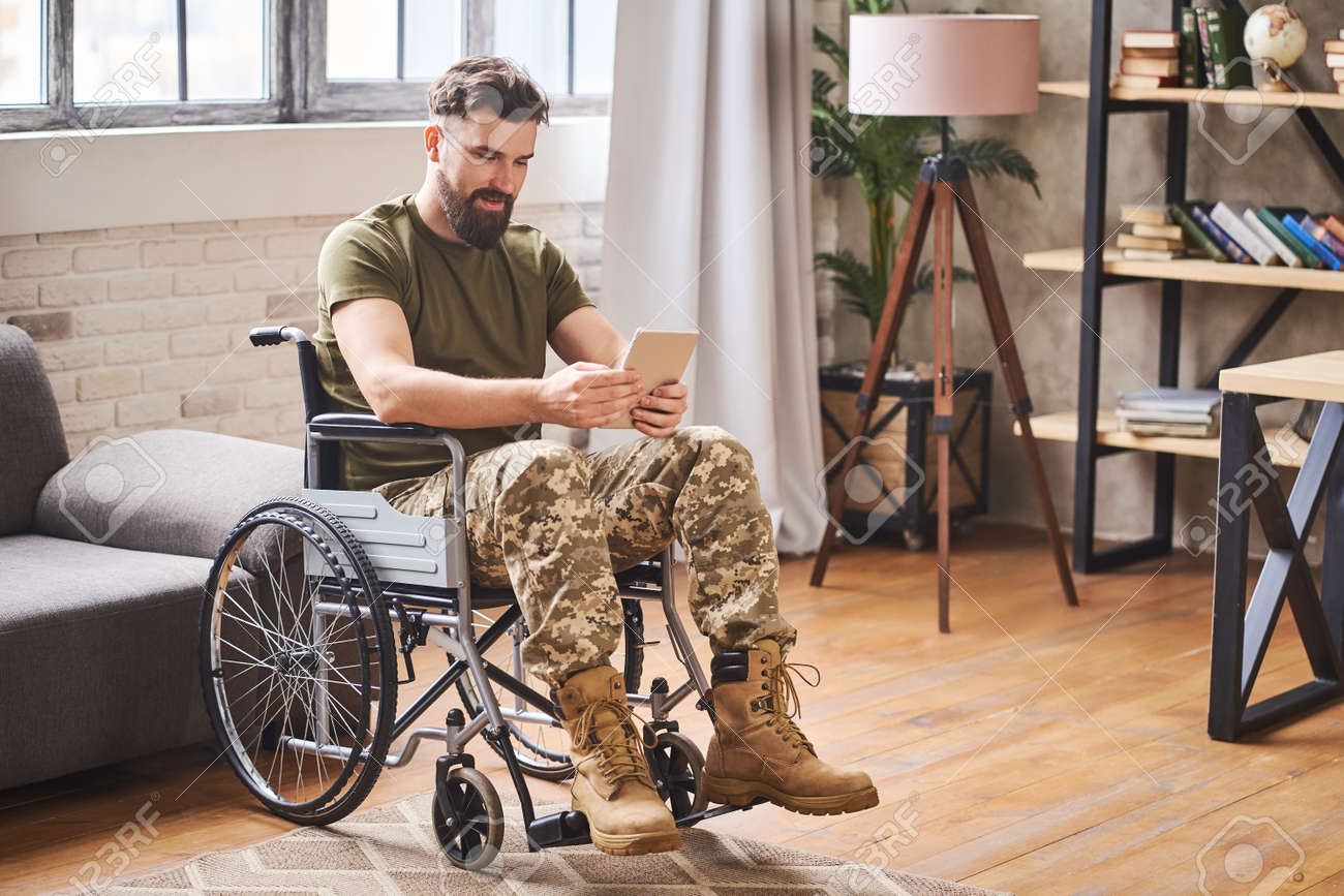 Disabled handsome military man sitting in a wheelchair and using a tablet - 172648650