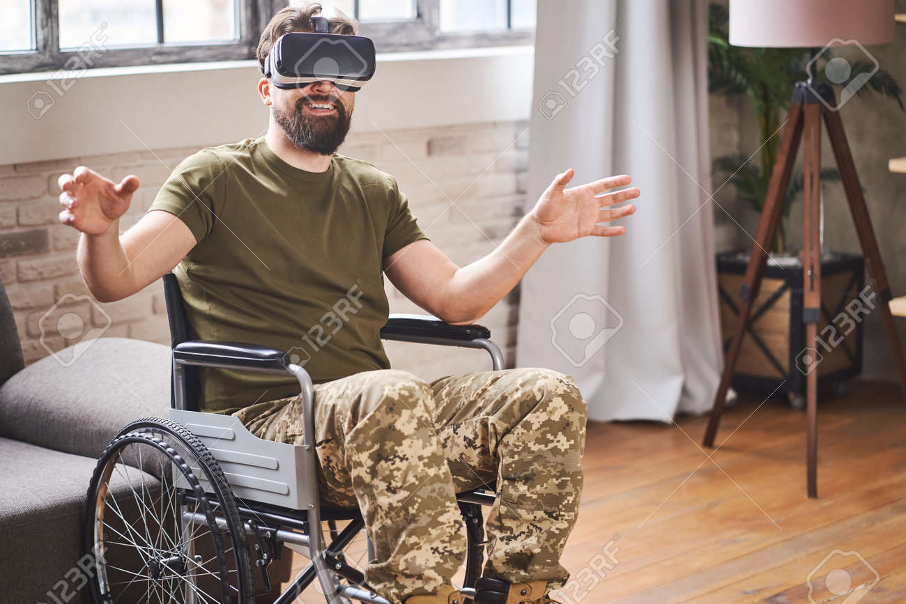 Joyful ex-serviceman sitting in a wheelchair and wearing a VR headset - 172648971