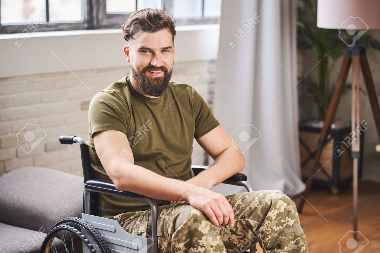 Disabled ex-serviceman wearing military uniform and sitting in a wheelchair - 173108073