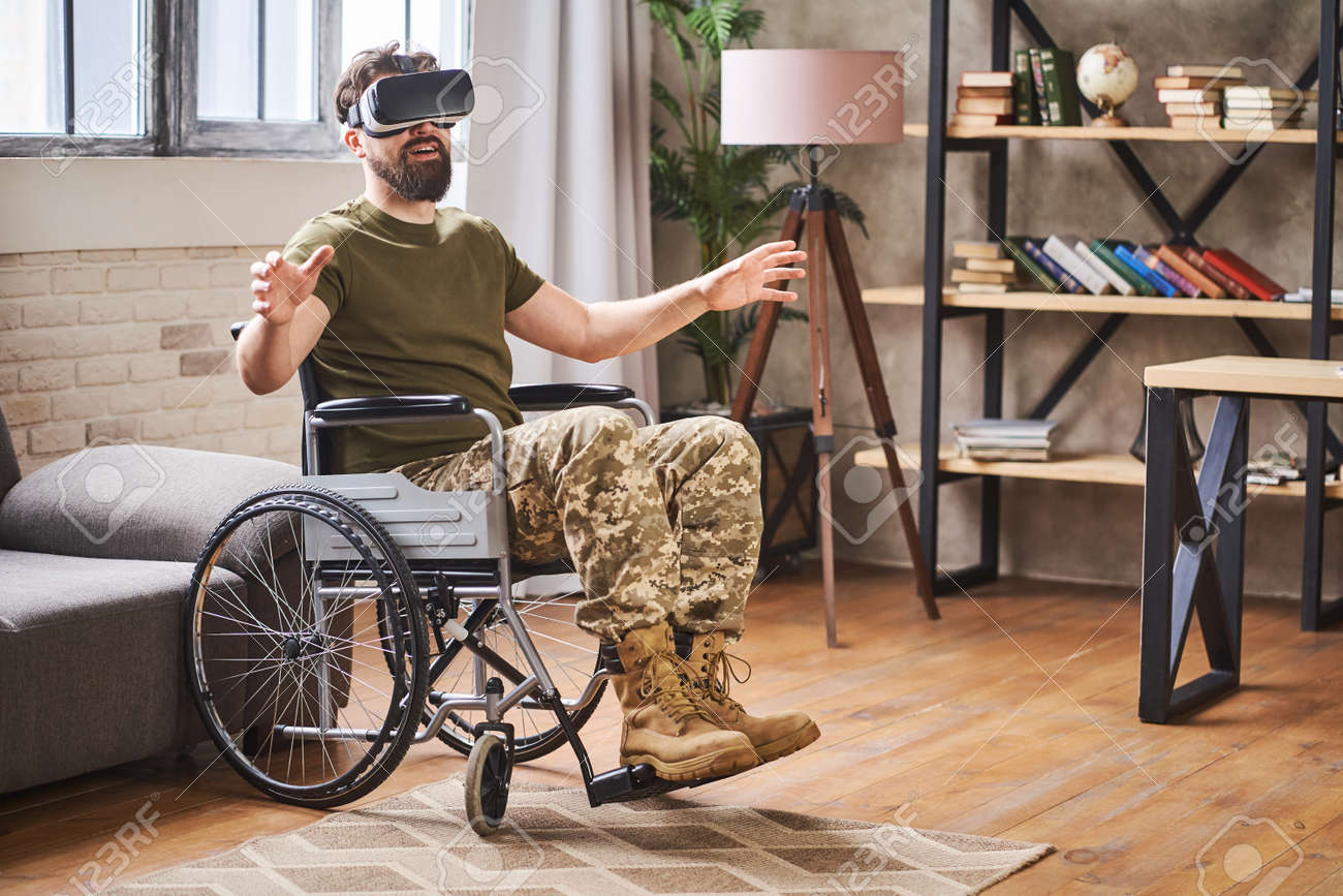 Military man sitting in a wheelchair and wearing a VR headset - 172649073