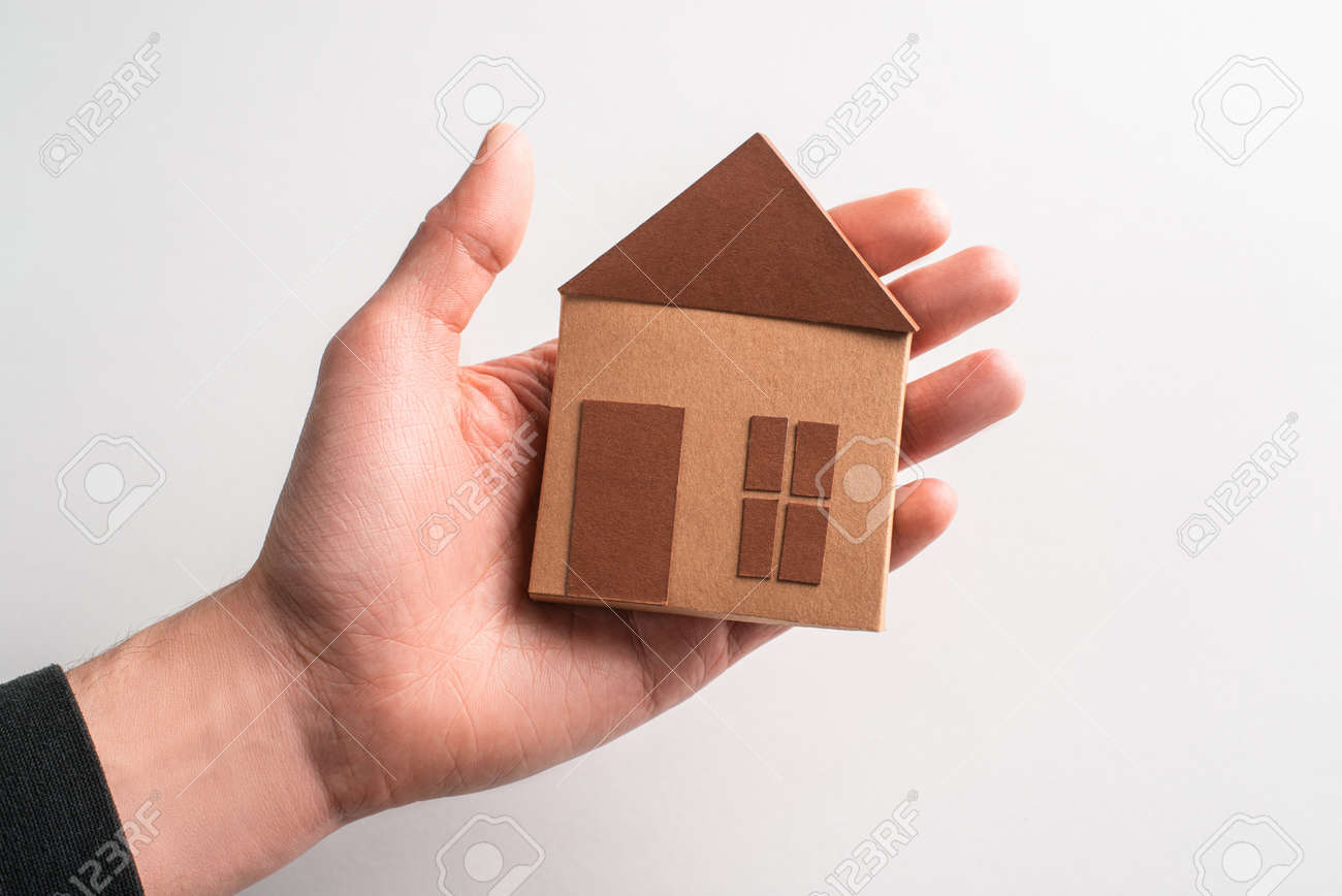 Cute brown paper house laying on a hand on white background - 173108129