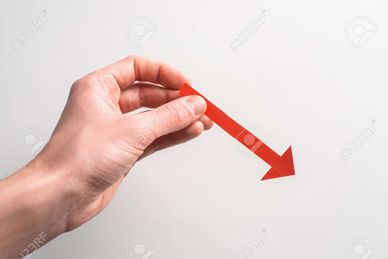 Hand holding a red paper arrow pointing down to the right - 172655884