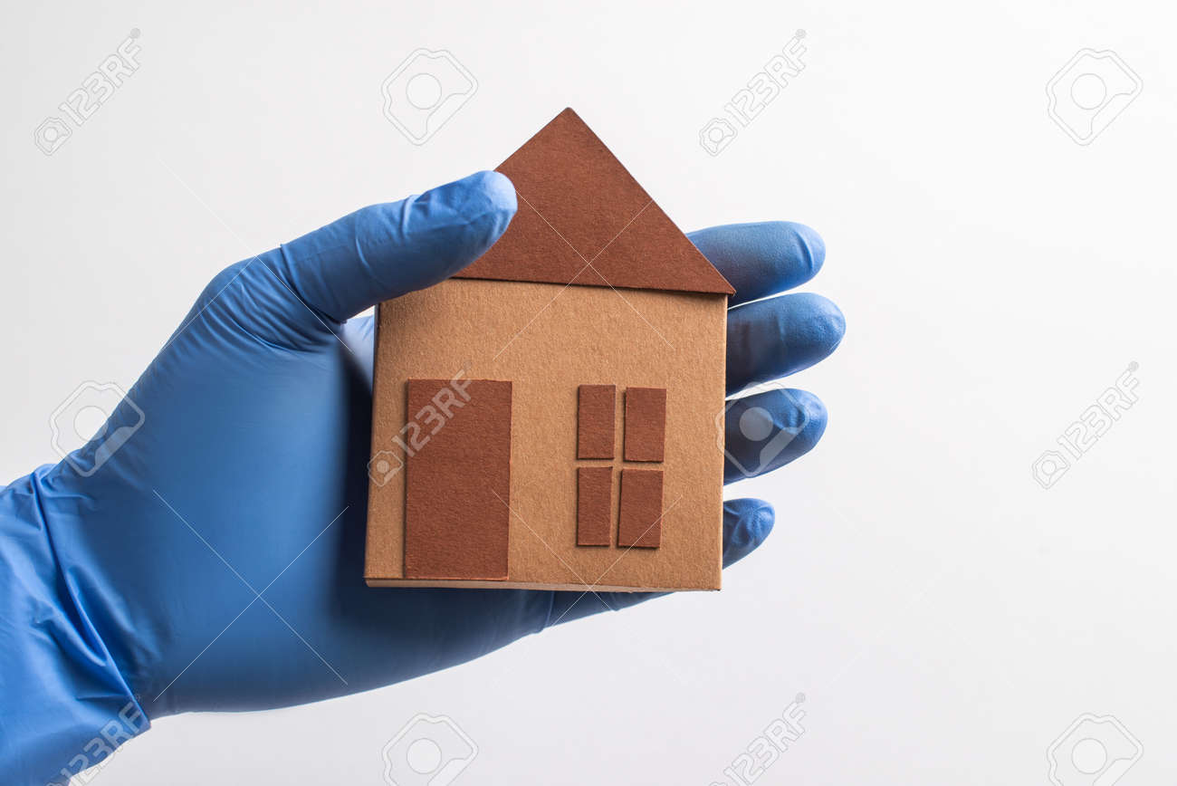 Hand in glove holding a paper house on white background - 173108130