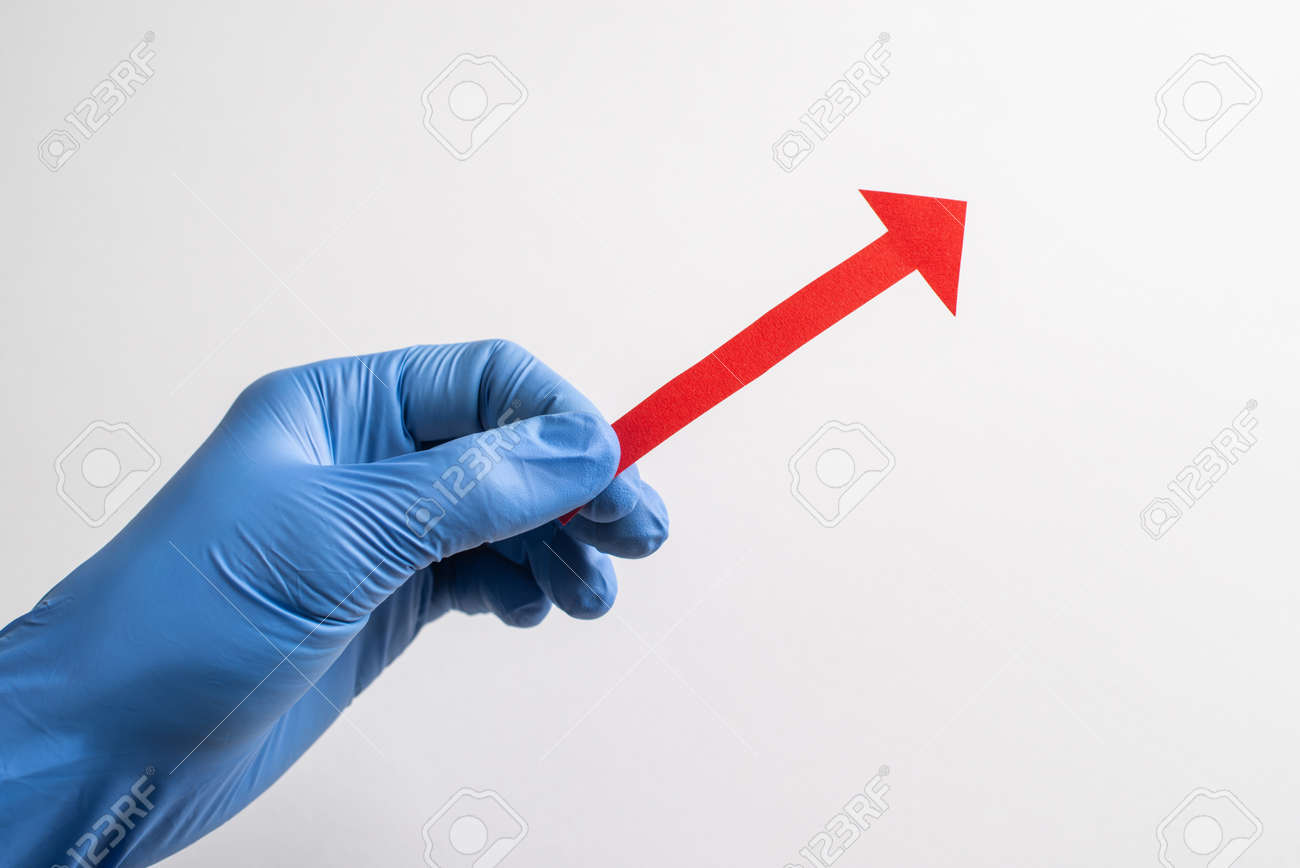 Hand in glove holding a red paper arrow pointing up to the right - 173108135