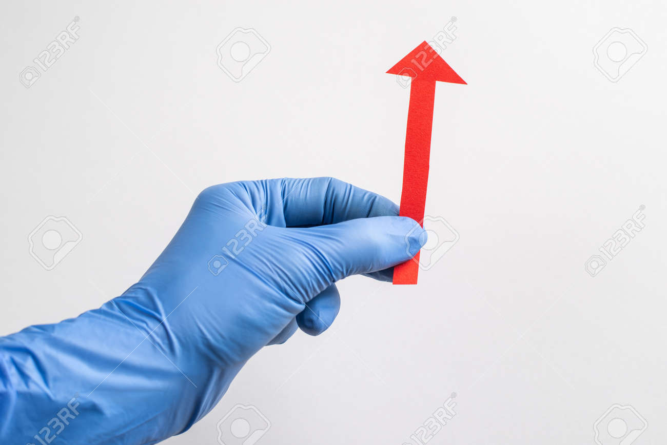 Hand in glove holding a red paper arrow pointing up on white background - 173108139