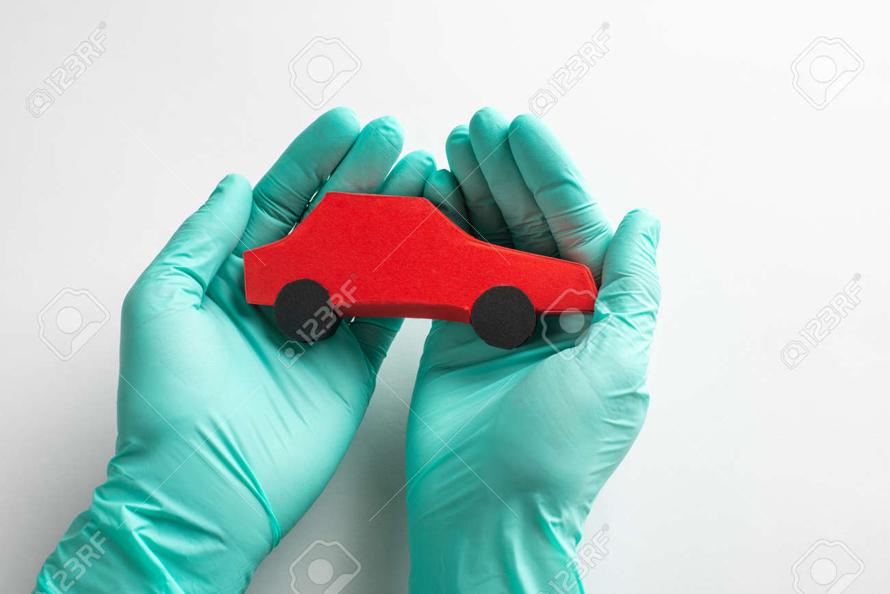 Hand in gloves holding a red paper car toy on white background - 173108144