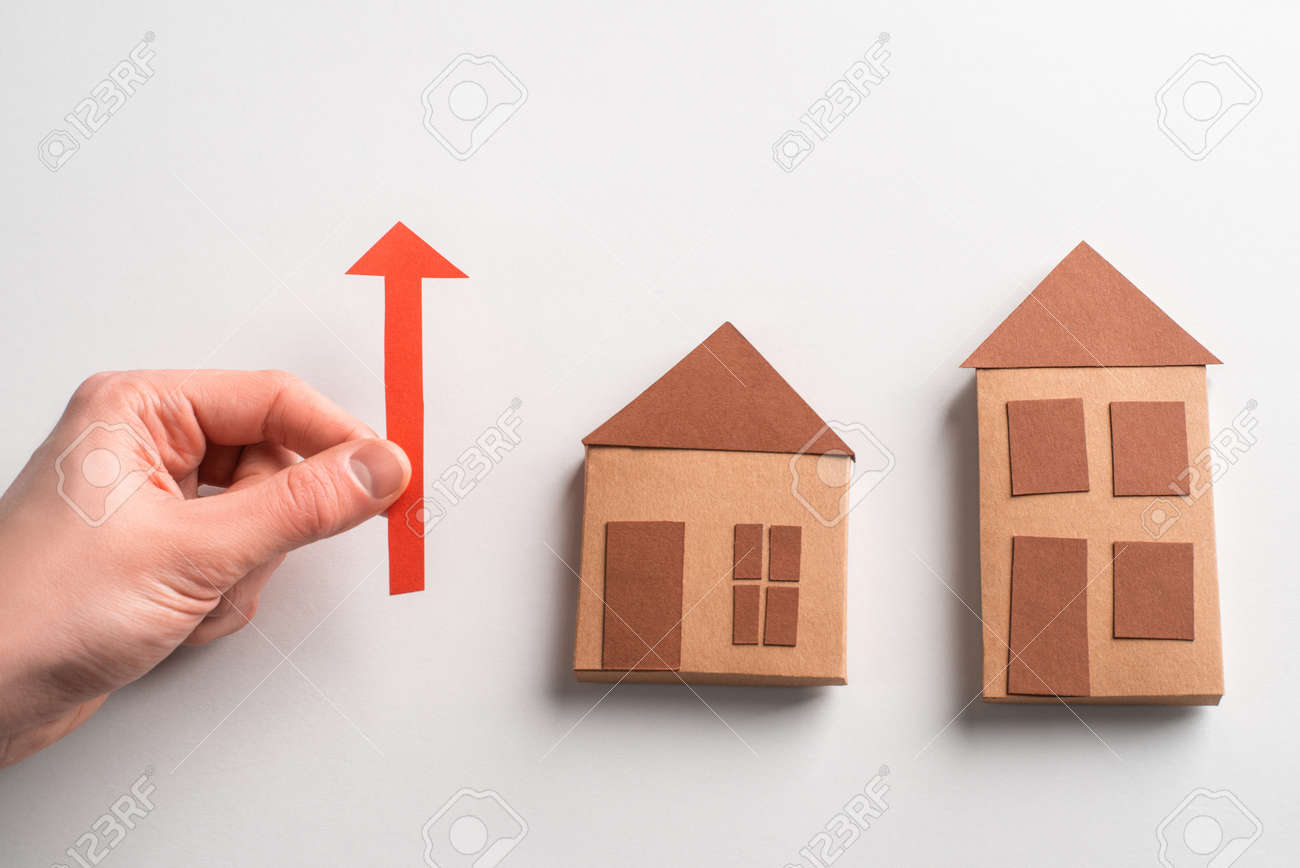 3d paper houses and hand holding a red arrow pointing up - 172655653