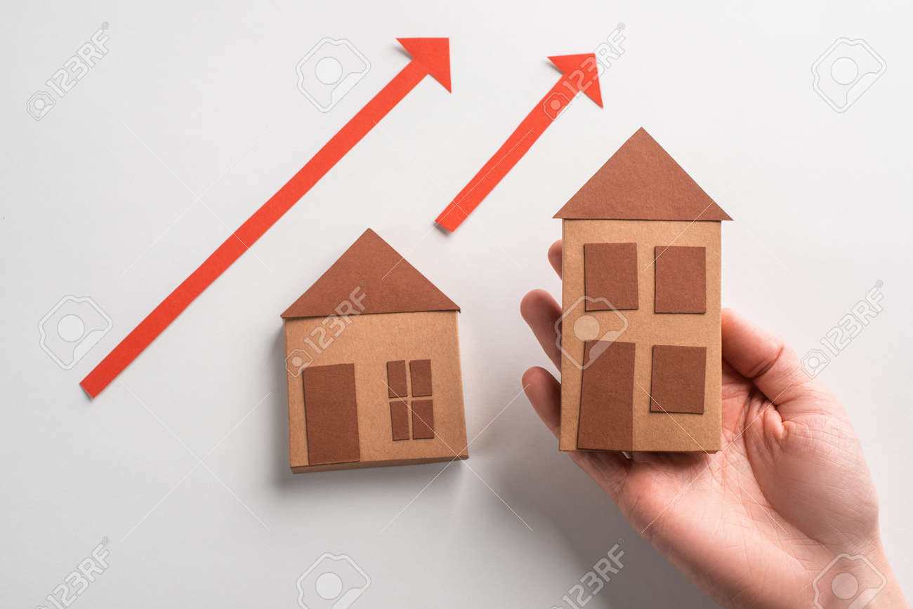 Hand putting 3d paper houses on chart with red arrows on white background - 173108147