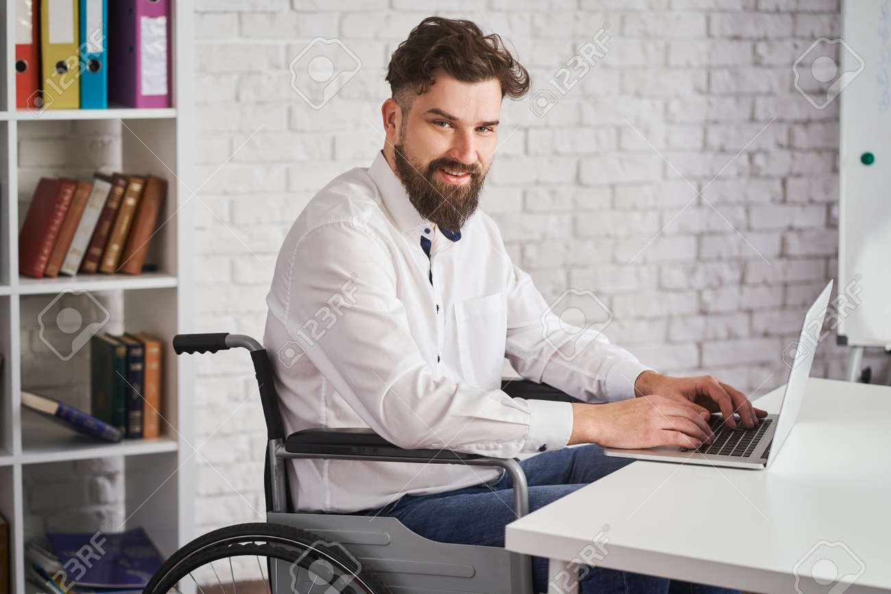 Portrait of a happy man working on a laptop and sitting on a wheelchair - 173108174