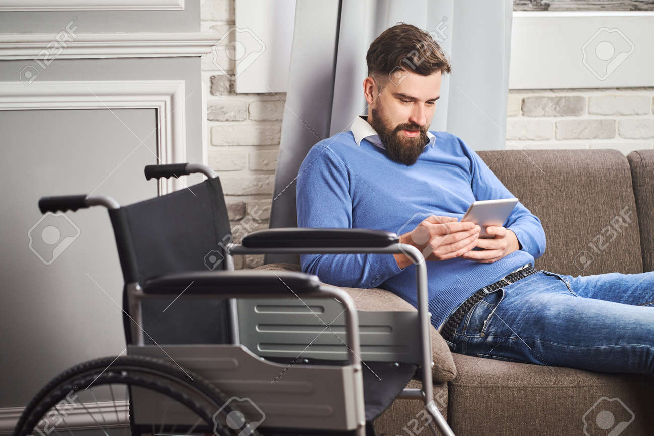 Man with disability resting on a couch and using a tablet computer - 173108182