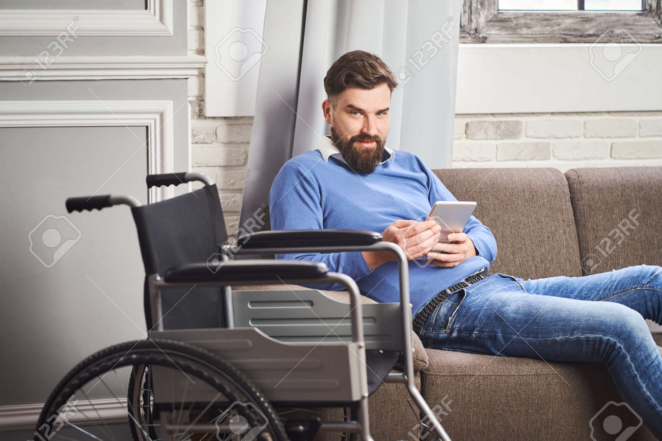 Portrait of a man with disability laying on a couch and using a tablet computer - 172760644