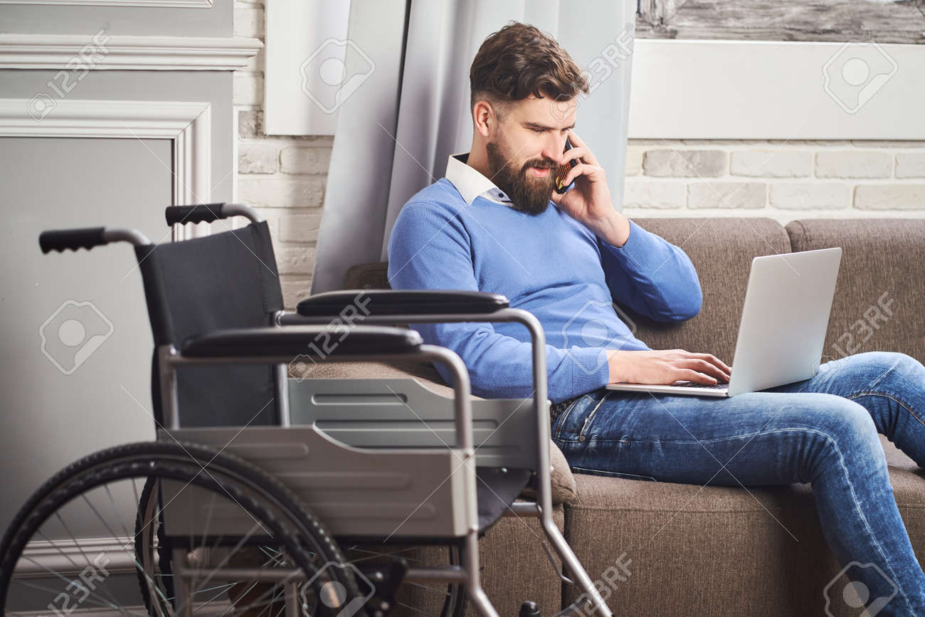 Disabled businessman sitting on a couch, working on a laptop, talking on a phone - 172760320