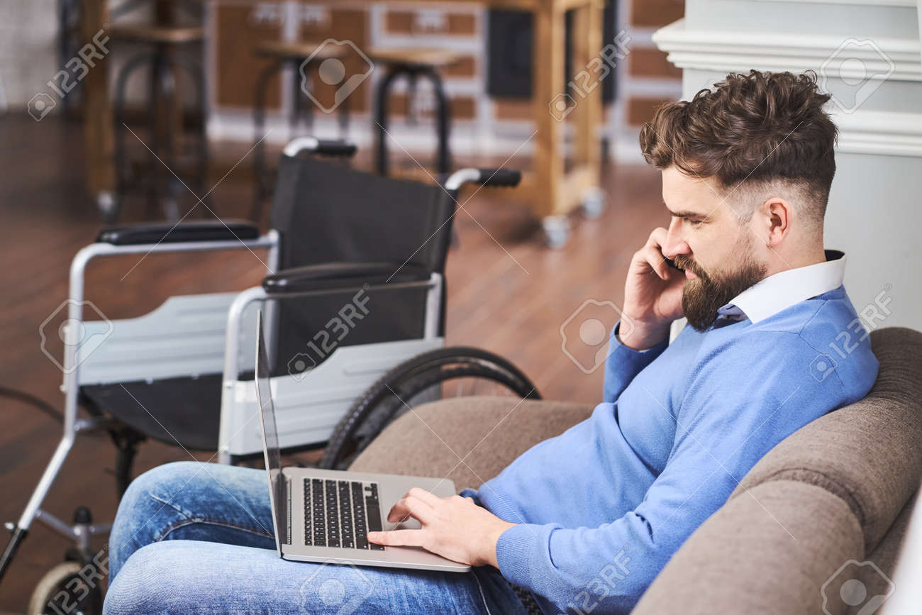 Successful businessman with disability sitting on a couch, working on a laptop - 173108180