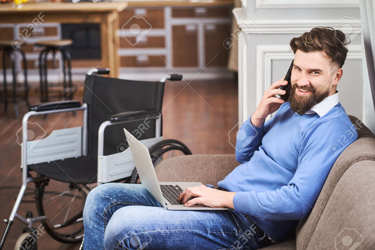 Cheerful disabled businessman sitting on a couch, working on a laptop - 172760690