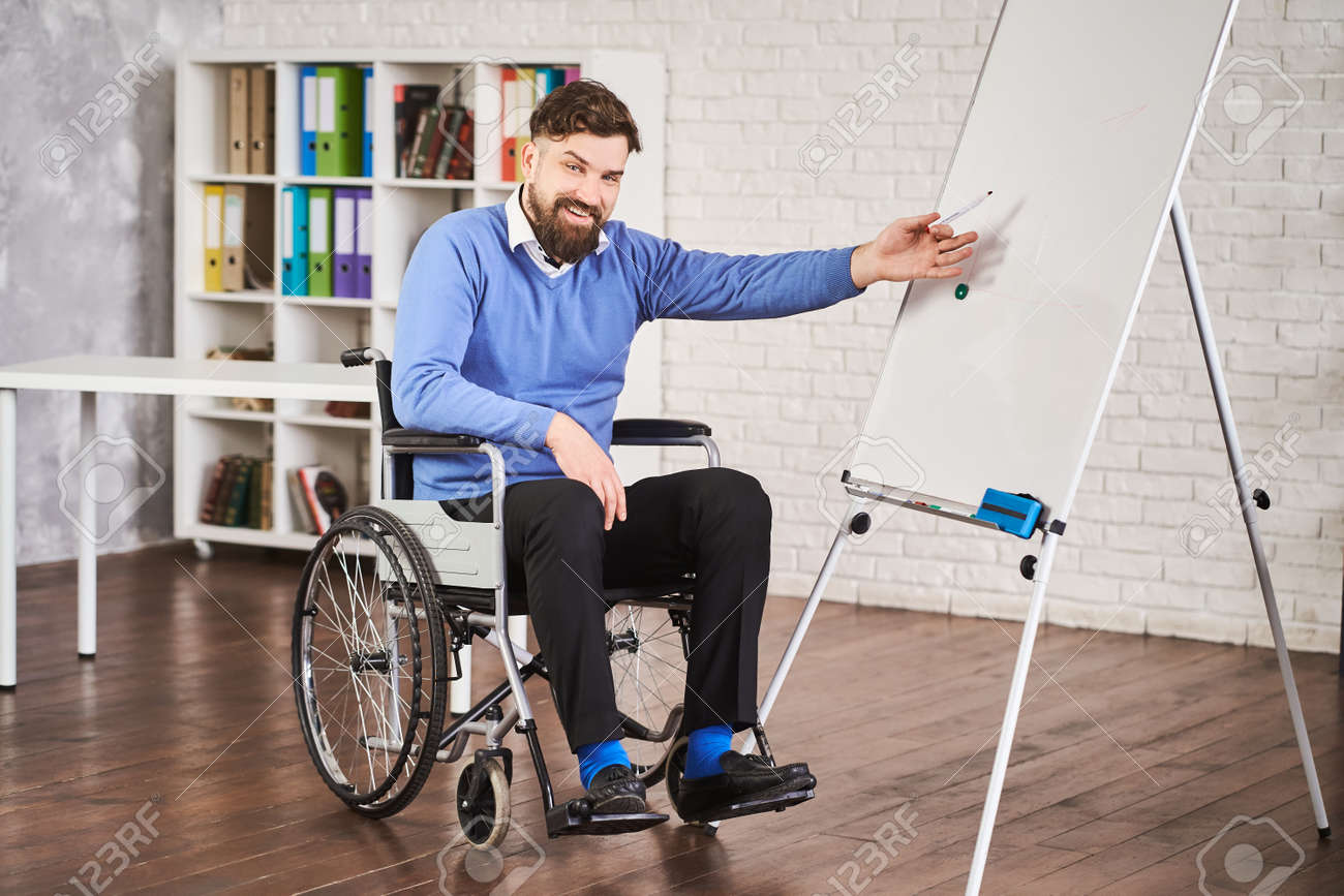 Disabled team leader using a board to draw chart and explaining - 172760688