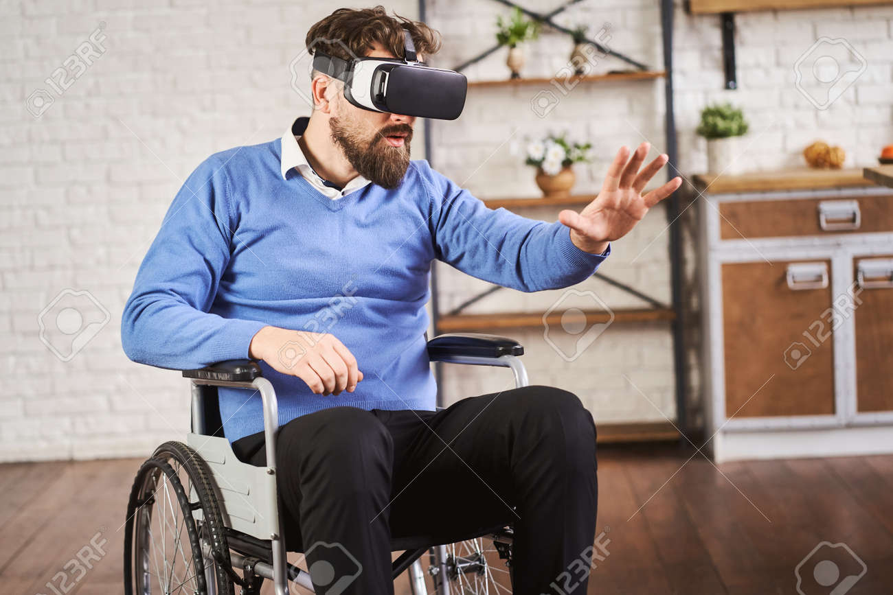 Man sitting in a wheelchair and wearing a VR headset - 172760928
