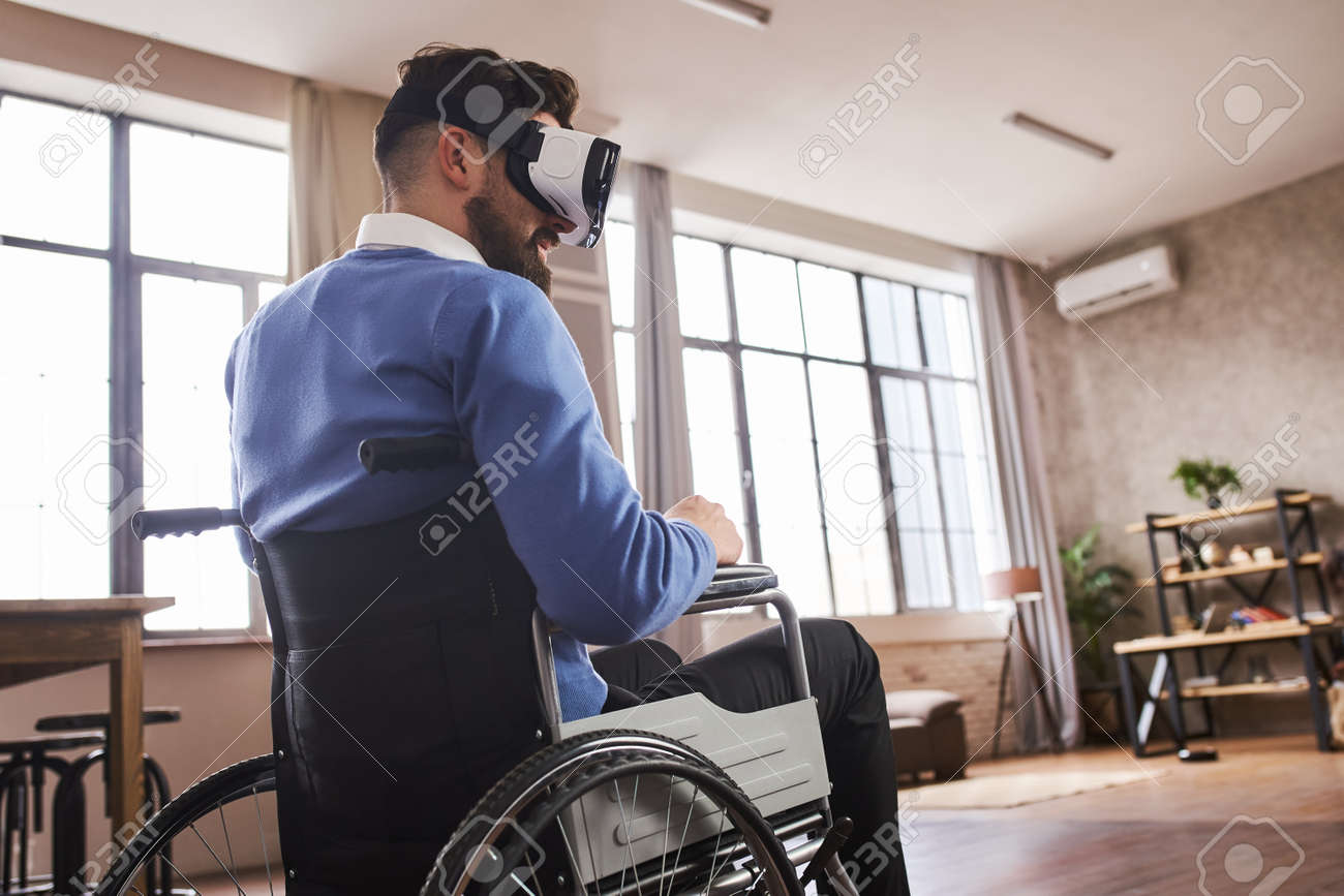 Man sitting in a wheelchair and wearing a VR headset at home - 172760798