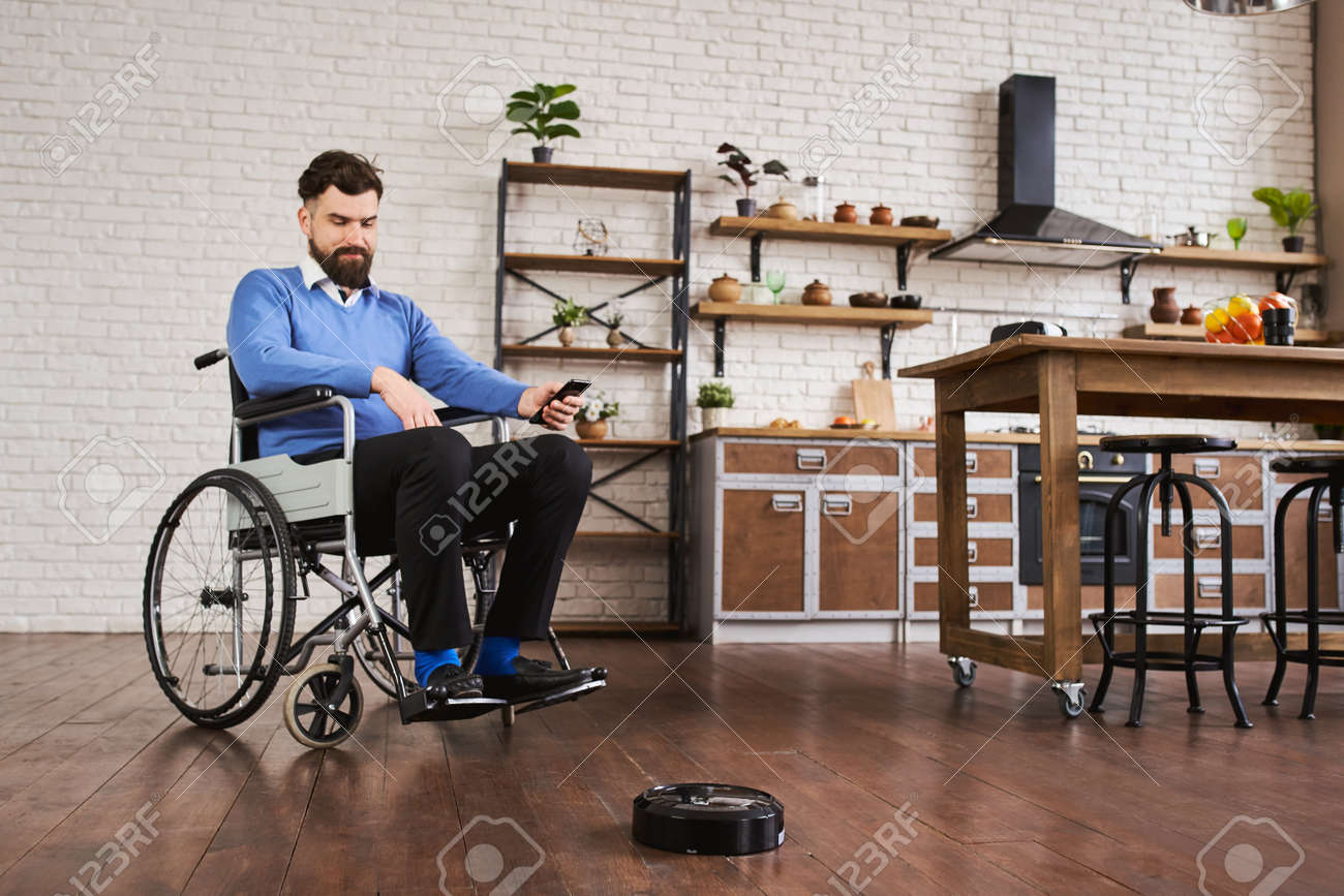 Man sitting in a wheelchair and using a robotic vacuum connected to his phone - 172760508