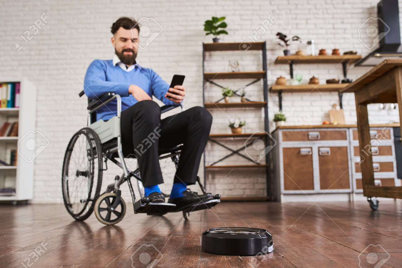 Man sitting in a wheelchair and using a robotic vacuum connected with a phone - 172760402