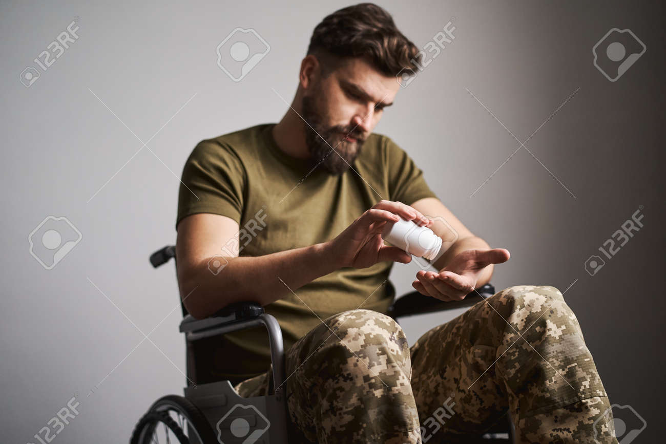 Saddened military man sitting in a wheelchair and holding a bottle of pills - 173108183