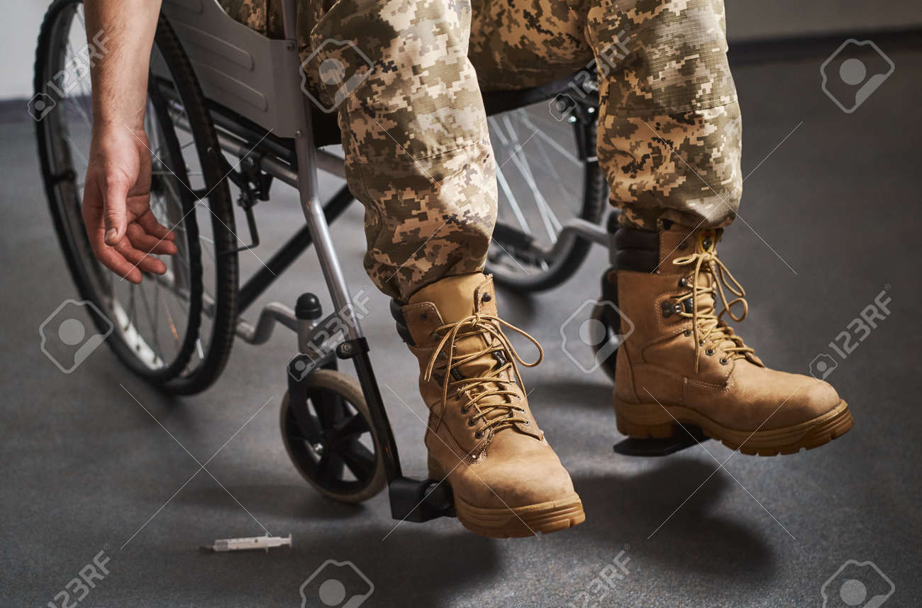 Disabled military man sitting in a wheelchair and cannot reach a fallen syringe - 173060136