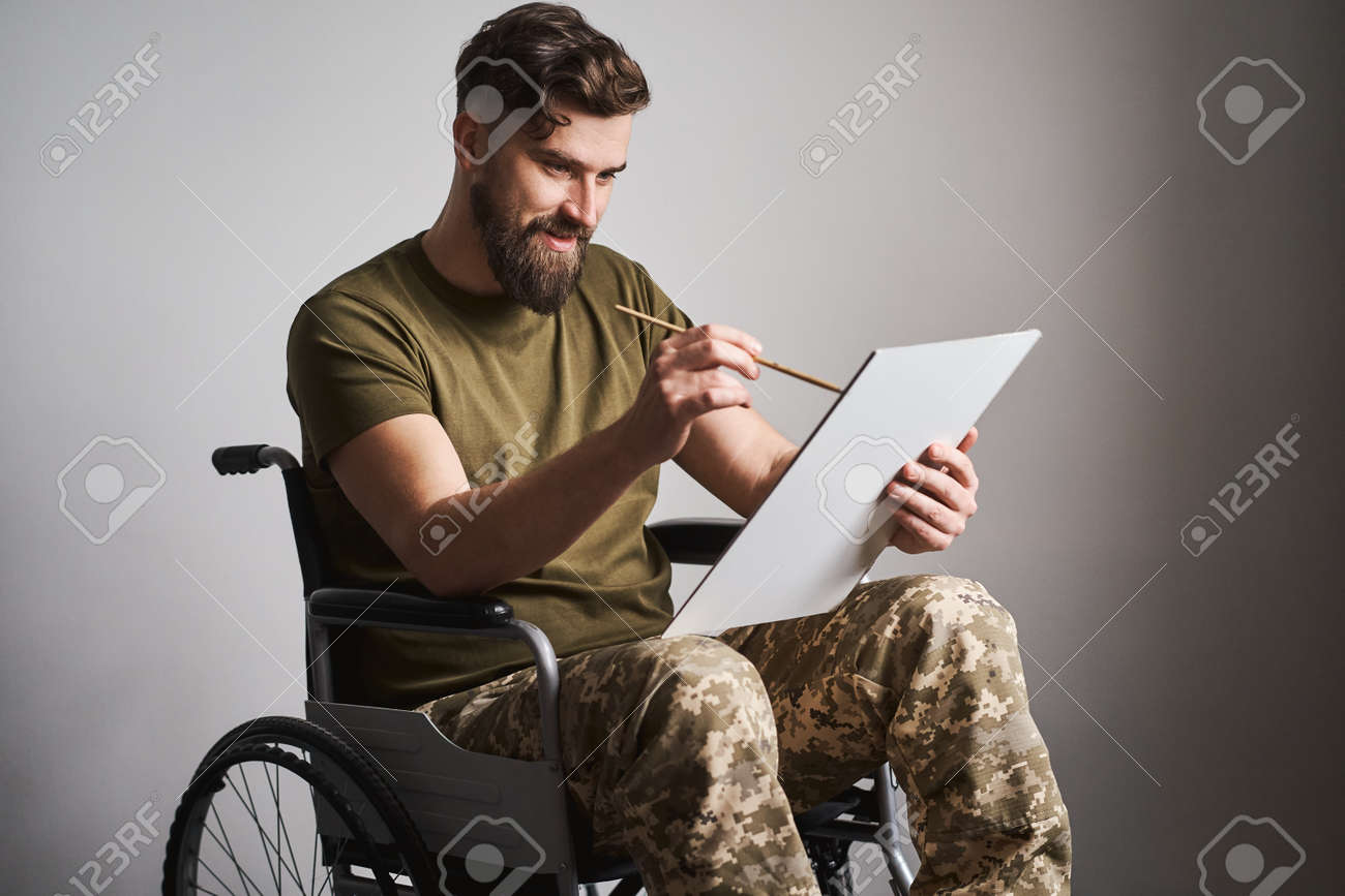Military man sitting in a wheelchair and painting a picture with a brush - 173059777