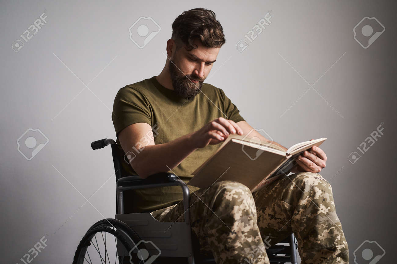 Ex-serviceman sitting in a wheelchair and reading a book - 173059852