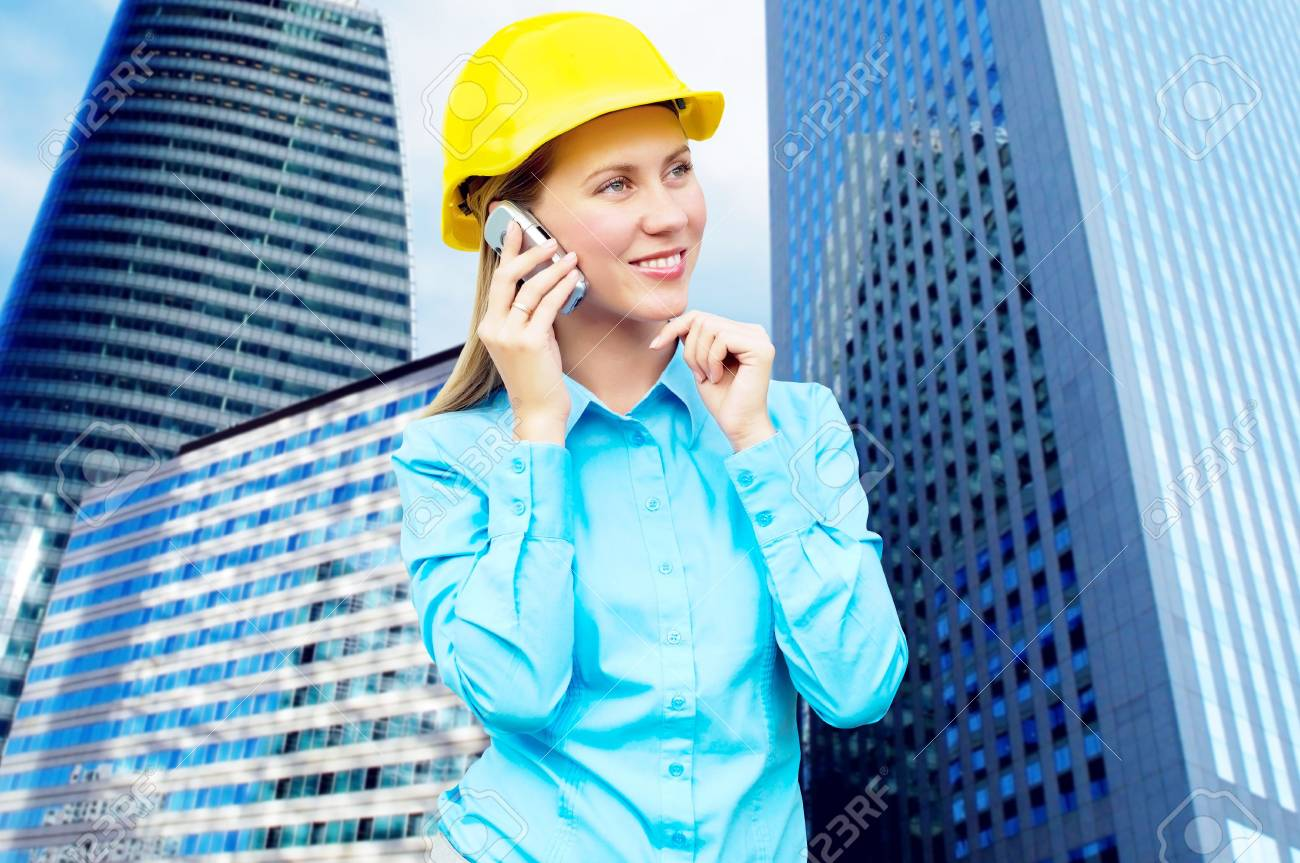 Young architect-woman wearing a protective helmet standing on the building background Stock Photo - 8114758