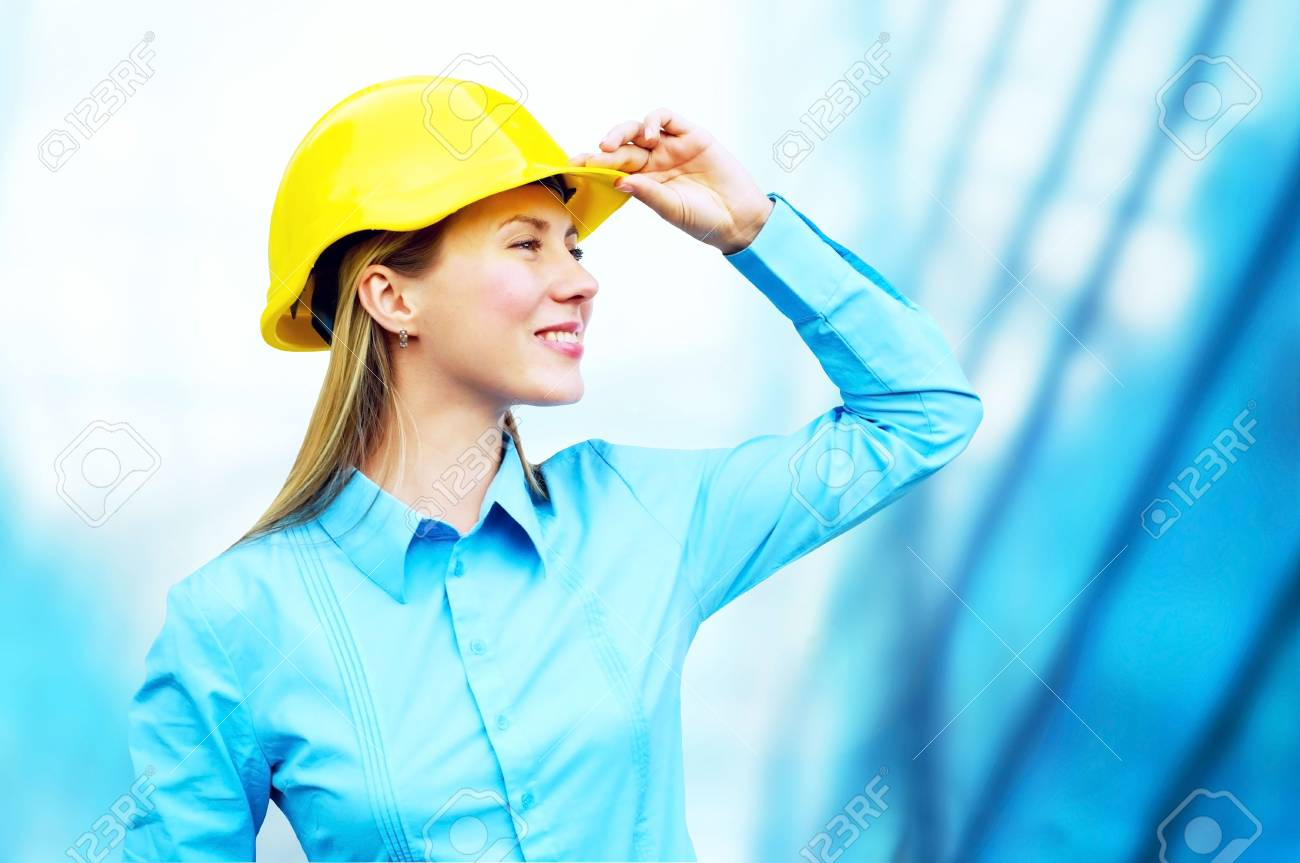 Young architect-woman wearing a protective helmet standing on the building background Stock Photo - 8172009