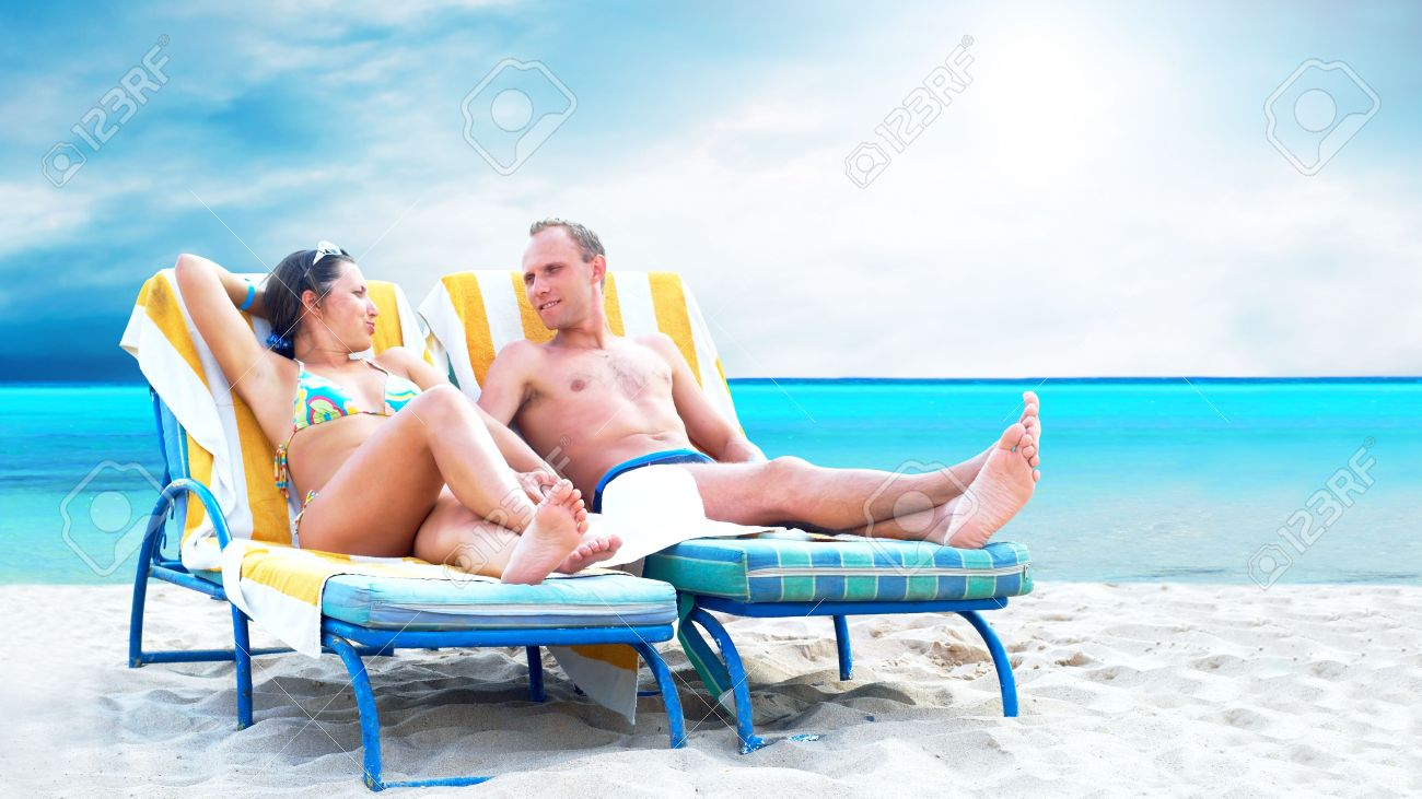 Rear view of a couple on a deck chair relaxing on the beach Stock Photo - 8174638